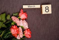 L'inscription le 8 mars avec des fleurs sur un fond gris Images libres de droits