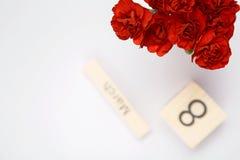 L'inscription le 8 mars avec les fleurs rouges sur un fond blanc Images stock