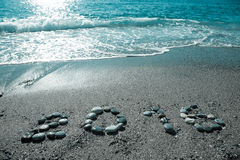 L'inscription 2016 par le petit caillou sur un littoral humide de sable modifié la tonalité Photos libres de droits