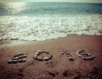 L'inscription 2016 par le petit caillou sur un littoral humide de sable modifié la tonalité Photographie stock