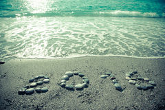L'inscription 2016 par le petit caillou sur un littoral humide de sable modifié la tonalité Photos stock