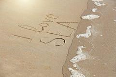 L'inscription que j'aime la mer est peinte sur le sable La vague lave o photos stock
