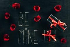 L'inscription SOIT LA MIENNE entourée avec des pétales de rose et des boîte-cadeau Photos stock