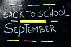 L'inscription sur l'asphalte avec la craie blanche de nouveau à l'école, aux marqueurs colorés et à la ligne jaune photos libres de droits