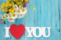 L'inscription sur l'amour en bois de fond au sujet des fleurs Images stock