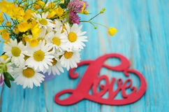 L'inscription sur l'amour en bois de fond au sujet des fleurs Image libre de droits
