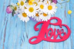 L'inscription sur l'amour en bois de fond au sujet des fleurs Photos libres de droits