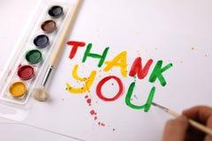 L'inscription sur la feuille de papier blanche avec des aquarelles vous remercient Images stock