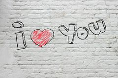 L'inscription sur le mur de briques blanc Photo libre de droits