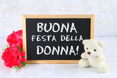 L'inscription sur le tableau en italien : Jour heureux du ` s de femme Fleurs et ours de nounours roses Photos libres de droits