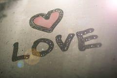 L'inscription sur le verre en sueur - amour et coeur rouge Photographie stock libre de droits