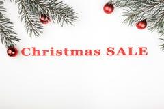 L'insegna di vendita di Natale su fondo bianco con i rami e l'albero sempreverdi gioca le decorazioni immagine stock