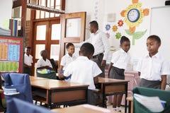 L'insegnante accoglie i bambini che arrivano all'aula della scuola elementare Fotografia Stock Libera da Diritti