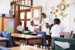 L'insegnante accoglie i bambini che arrivano all'aula della scuola elementare Immagine Stock