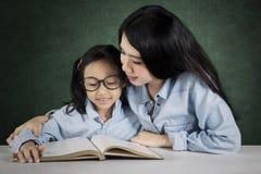 L'insegnante aiuta il suo studente a leggere un libro Fotografia Stock