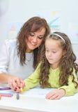 L'insegnante aiuta la bambina Immagine Stock
