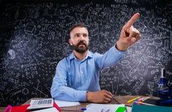L'insegnante allo scrittorio, rifornimenti di scuola, ha alzato il dito, grande lavagna Immagini Stock Libere da Diritti
