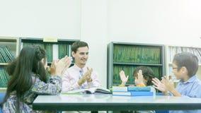 L'insegnante caucasico sorridente ed il raggruppamento dell'asiatico scherza lo studente lear Immagine Stock Libera da Diritti