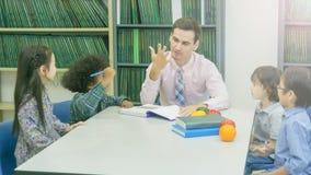 L'insegnante caucasico sorridente ed il raggruppamento dell'asiatico scherza lo studente lear Immagine Stock