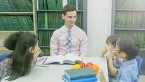 L'insegnante caucasico sorridente ed il raggruppamento dell'asiatico scherza lo studente lear Fotografia Stock