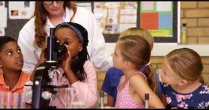 L'insegnante che assiste la scuola scherza con l'esperimento in laboratorio stock footage