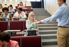 L'insegnante che dà l'esame prova agli studenti alla conferenza Immagini Stock
