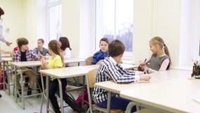 L'insegnante che dà le penne alla scuola scherza in aula video d archivio