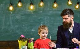 L'insegnante con la barba, il padre insegna al piccolo figlio ad assorbire l'aula, lavagna su fondo L'artista di talento passa il fotografia stock libera da diritti
