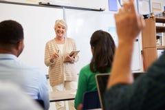 L'insegnante con la compressa e gli studenti ai corsi per adulti classificano fotografie stock libere da diritti
