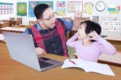 L'insegnante dà l'ordine sul suo studente pigro allo studio Immagini Stock