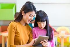 L'insegnante della donna dell'Asia insegna alla studentessa con il computer della compressa in Cl Immagini Stock Libere da Diritti