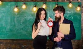 L'insegnante di signora ed il maestro rigoroso si preoccupano per disciplina e le regole a scuola Uomo con il libro della tenuta  fotografie stock libere da diritti