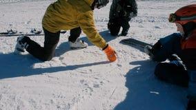 L'insegnante di snowboard spiega agli studenti la tecnica di snowboard, disegnante diagrams sulla neve video d archivio