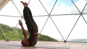 L'insegnante di yoga esegue il asana che sta sulle spalle con i suoi vantaggi archivi video