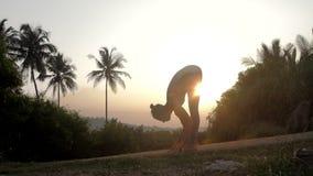 L'insegnante di yoga piega il corpo alle ginocchia al movimento lento dell'alba video d archivio