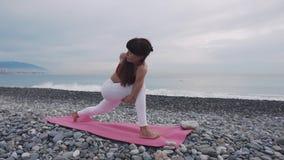 L'insegnante di yoga sta dimostrando i asanas sulla riva del ciottolo del mare, donna allegra archivi video