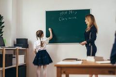 L'insegnante e l'allievo di lezione della scuola scrivono su una lavagna Fotografia Stock