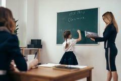 L'insegnante e l'allievo di lezione della scuola scrivono su una lavagna Fotografie Stock Libere da Diritti