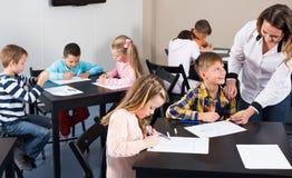 L'insegnante e l'età elementare scherza il disegno all'aula Immagini Stock Libere da Diritti