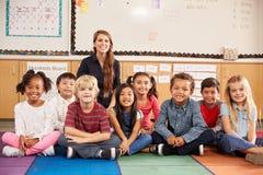 L'insegnante e la scuola elementare scherza la seduta sul pavimento dell'aula Immagini Stock