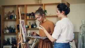 L'insegnante e lo studente di arte delle giovani donne stanno dipingendo insieme, stanno parlando e sorridendo durante la classe  archivi video