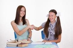 L'insegnante e lo studente stringono felicemente le mani a vicenda Immagine Stock