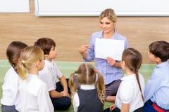 L'insegnante ed i bambini stanno sedendo insieme nel cerchio Immagine Stock Libera da Diritti