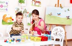 L'insegnante ed il ragazzo imparano il tiraggio nella stanza del gioco. fotografia stock libera da diritti
