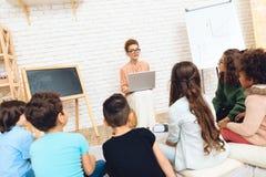 L'insegnante elegante con il computer portatile conduce la lezione dell'aula a scuola educativa Fotografie Stock Libere da Diritti