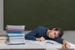 L'insegnante esaurito e sovraccarico sta dormendo sullo scrittorio in aula Fotografia Stock