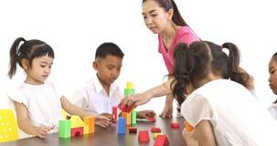 L'insegnante gioca i blocchi di legno variopinti con lo studente stock footage
