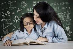L'insegnante guida il suo studente per leggere un libro Fotografie Stock