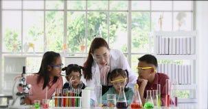 L'insegnante insegna agli studenti circa i prodotti chimici in laboratorio video d archivio