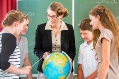 L'insegnante istruisce gli studenti che hanno lezioni di geografia a scuola Immagini Stock